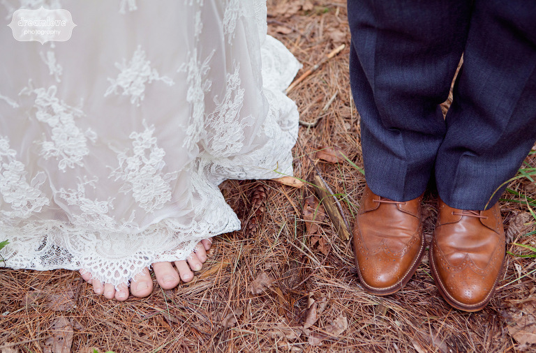 A barefoot bride standing on pine needles on her wedding day.