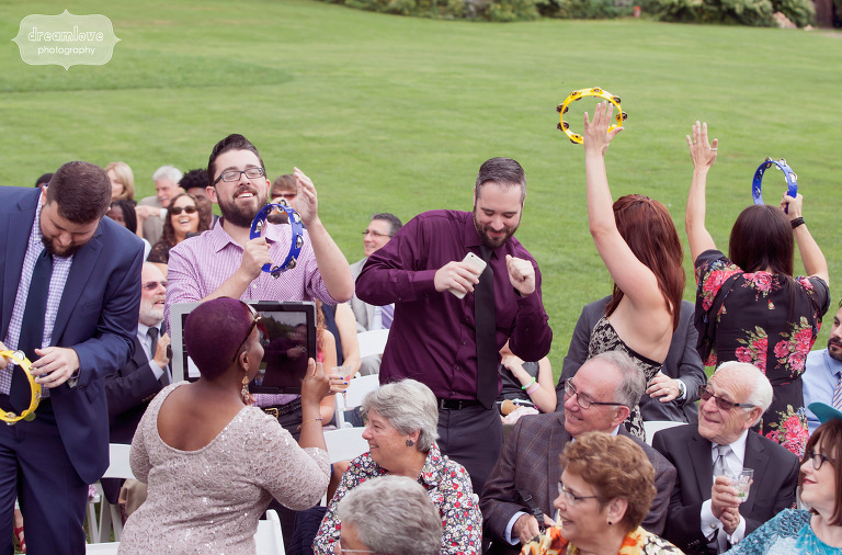 Wedding guests danced and play tambourines as the bride and groom walked down the aisle together.