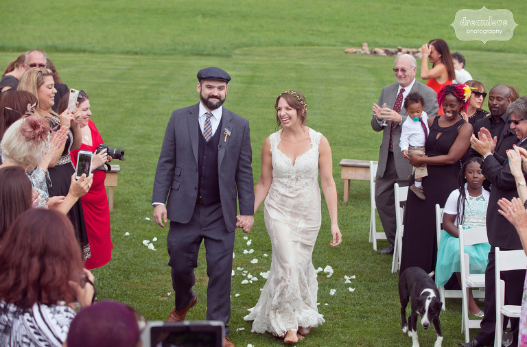 Bride and groom smile as the process down the aisle of their outdoor wedding at the Lareau Farm Inn.