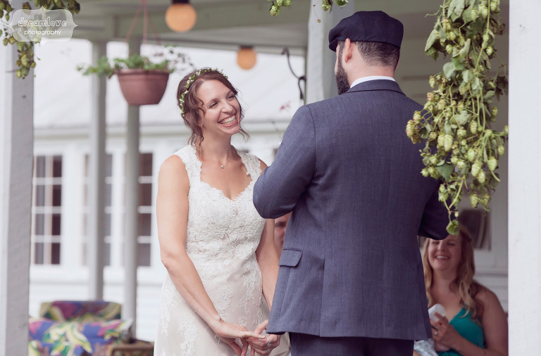 A bride smiles while listening to groom reading his vows at a back porch wedding in Vermont.