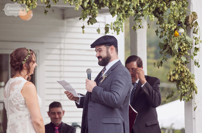 A happy couple read their vows while surrounded by a floral arrangement during their back porch wedding.