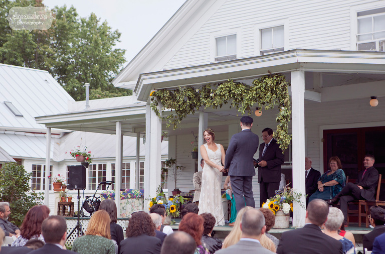 Wedding guests laugh during an outdoor wedding ceremony at the Lareau Farm Inn.