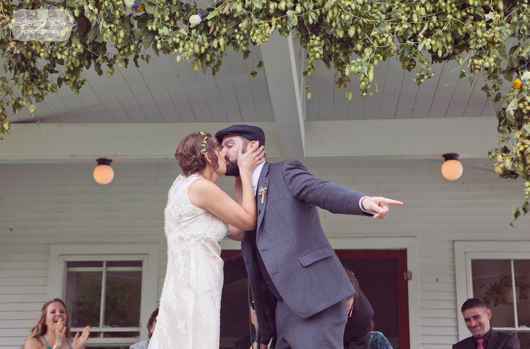 Bride and groom kiss under a unique floral arrangement that included hops and flowers.