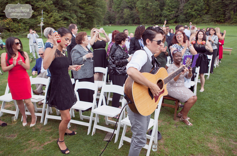 Wedding guests play music from their seats during an outdoor ceremony in Vermont.