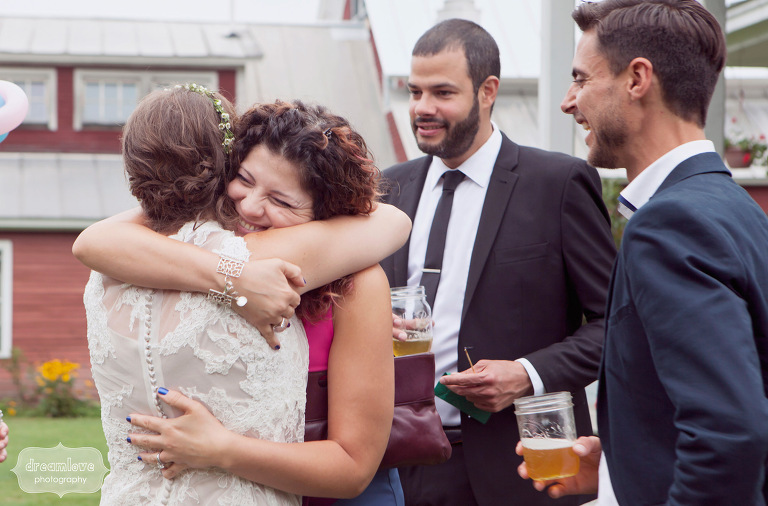 A happy wedding guest hugs the bride following an outdoor ceremony.