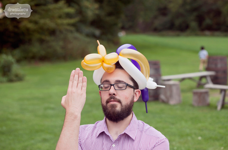 A wedding guest entertains the children while wearing balloons on his head.