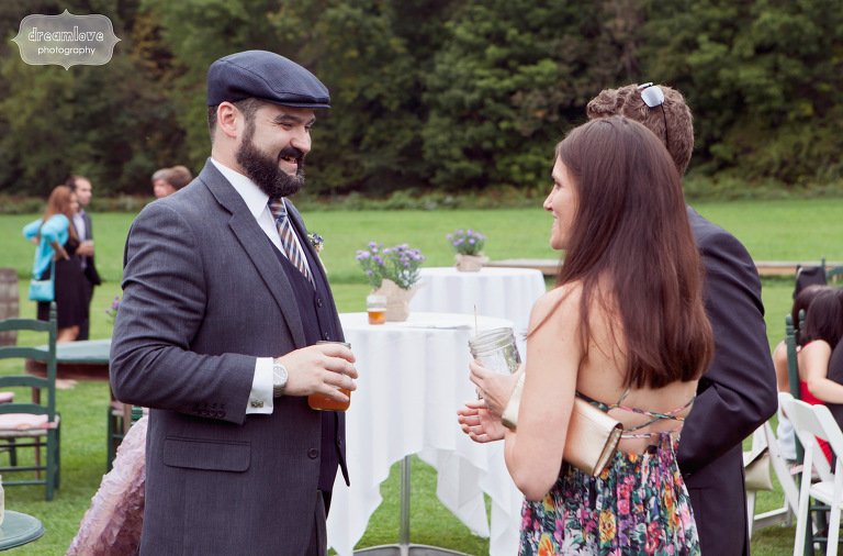 A groom laughing with wedding guests during the cocktail hour.