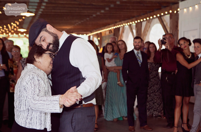 A mother and son wedding dance under twinkle lights in the fall.