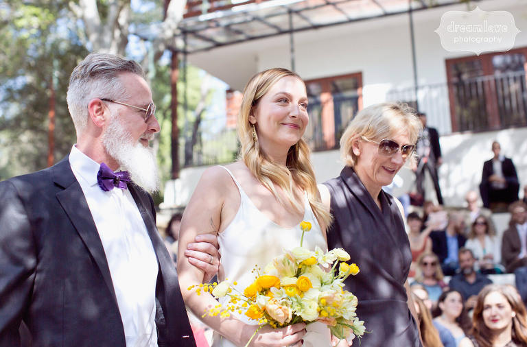 The bride is accompanied by her parents down the aisle at the 1909 in Topanga, CA.