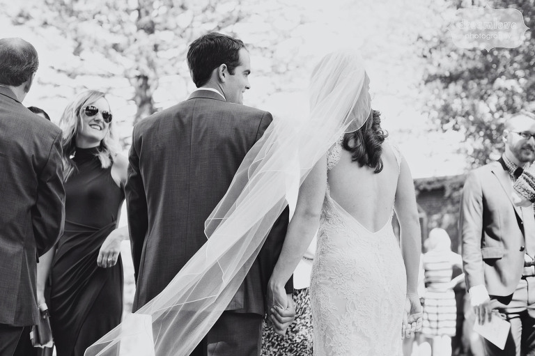 Artistic black and white photo of bride and groom with guests at their outdoor wedding at the Hildene in Manchester, VT.