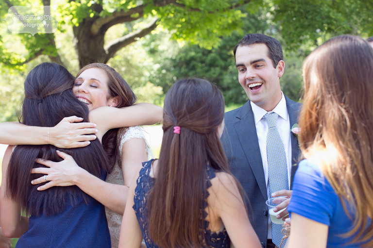 Bride and groom hug guests during their receiving line at the St. Paul's Church in Manchester, VT.