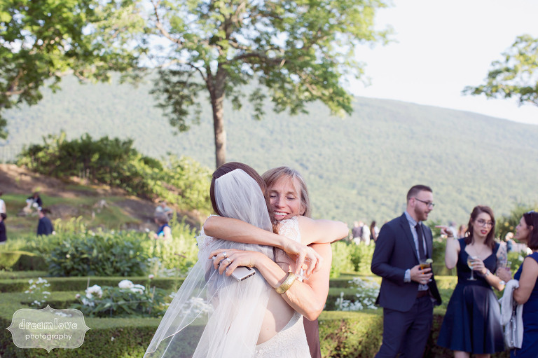 Great candid moment of wedding guest hugging the bride at the Hildene in VT.