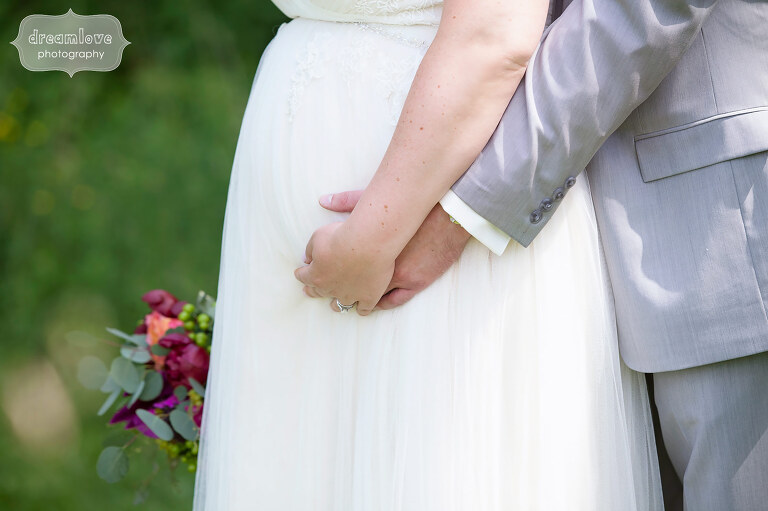 Sweet candid photo of the groom's hand on the bride's belly for this six month pregnant couple at the Sugarbush Resort in VT.