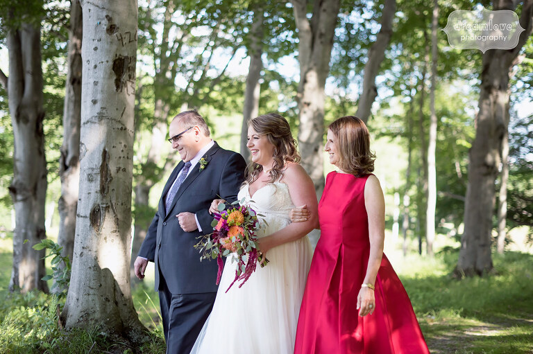 The bride is accompanied by her parents to walk down the aisle before her summer Sugarbush, VT wedding.
