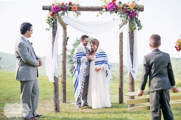 The bride and groom are wrapped in a blanket under the chuppah during their Jewish wedding ceremony at Sugarbush, VT.
