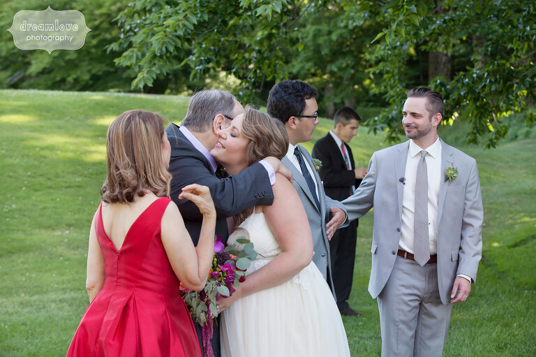 Documentary wedding photography of bride and groom hugging their parents after their June ceremony at Sugarbush in VT.