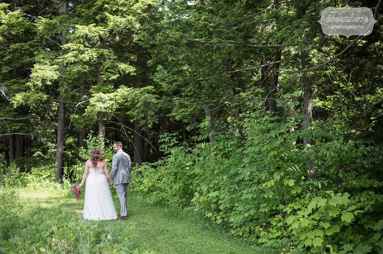 Documentary wedding photography of the bride and groom walking down a path after their Sugarbush Resort wedding in VT.