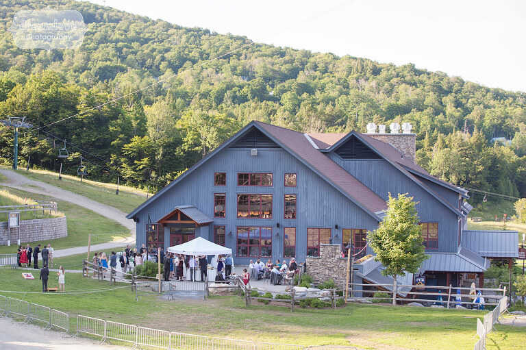 View of the cocktail hour outside of the wedding reception barn at the Sugarbush Resort in VT.