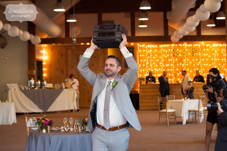 Funny photo of the groom holding up a boombox from Say Anything movie during wedding reception at Sugarbush, VT.