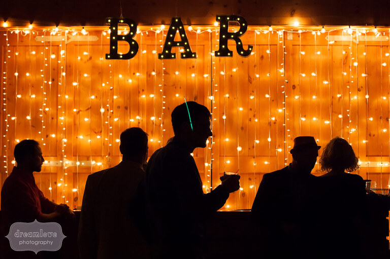Artistic wedding photo of silhouettes against this rustic twinkle light bar at Sugarbush, VT.