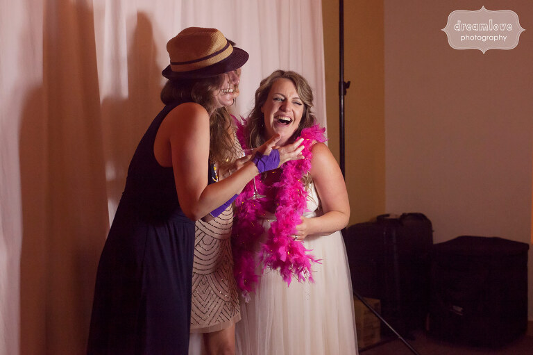 The bride laughing with friends in the photo booth at her Sugarbush, VT wedding.