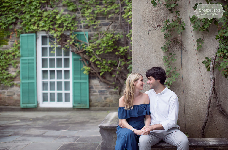 Cute natural engagement photo of couple sitting down with ivy in Hyde Park, NY.