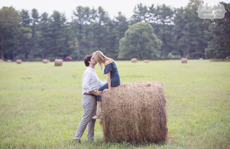 Couple kissing on a hay bale during an engagement photo session in FDR Park in Hudson Valley.