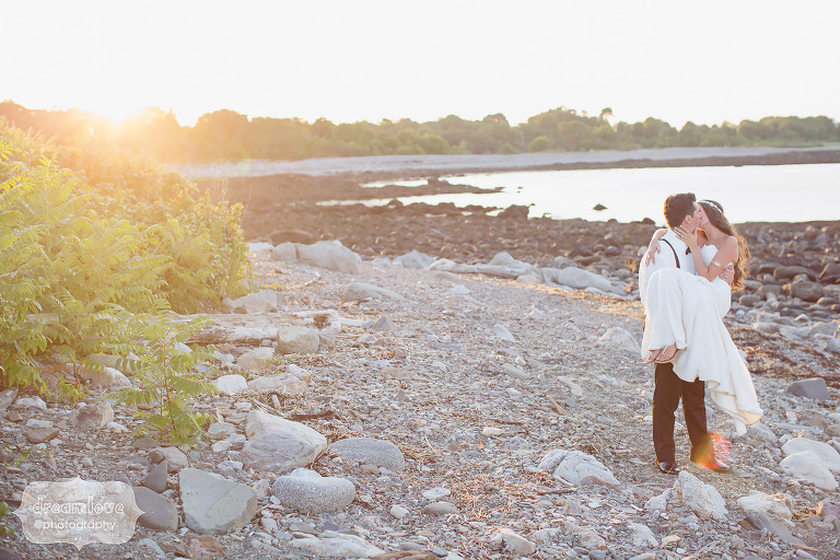 Groom picking up bride at sunset on Odiorne State Park beach in NH.