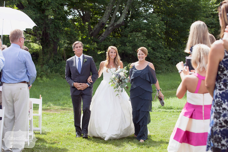 Bride walking down the aisle photo with both of her parents during her summer outdoor wedding at the 1824 House in VT.