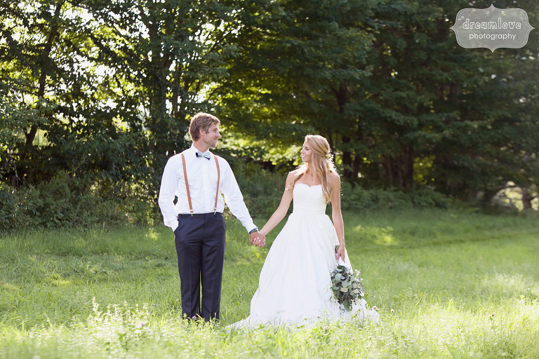 Summer wedding at the 1824 House in Vermont with the bride and groom holding hands in a field.