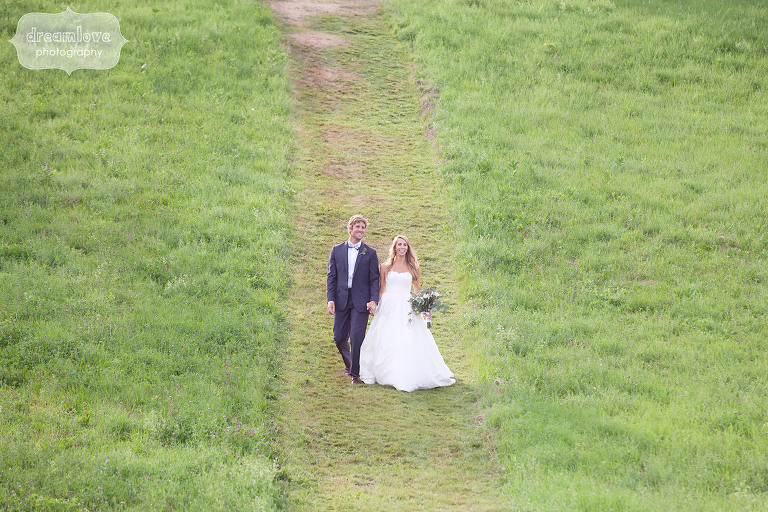 Natural portrait of the bride and groom walking through field at the 1824 House in VT.