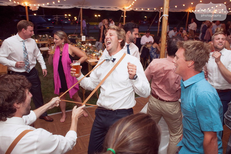 Funny photo of a wedding guest pulling the groom's suspenders while dancing at the 1824 House in VT.