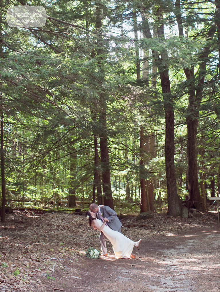 The groom dips the bride in the woods at the Woodbound Inn for this NH camp wedding.