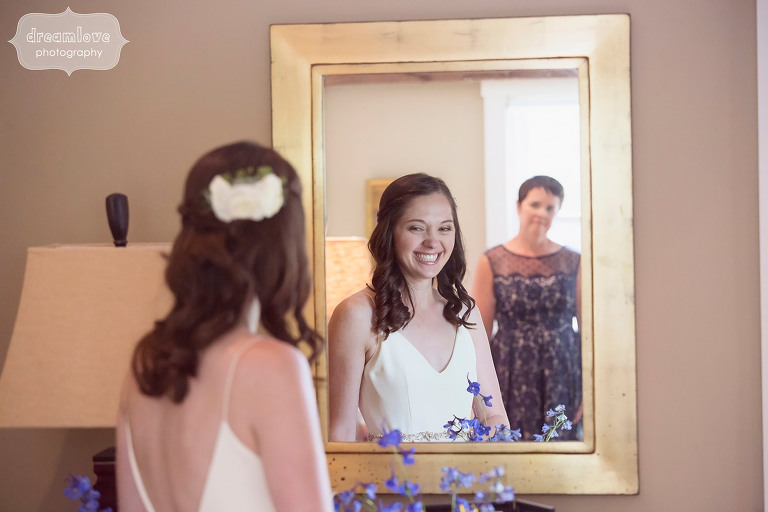 The bride looks in the mirror with her mom behind her at the Woodbound Inn camp wedding venue in NH.