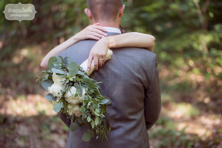 Love this photo of the bride with her arms around the groom's neck and her bouquet behind him.