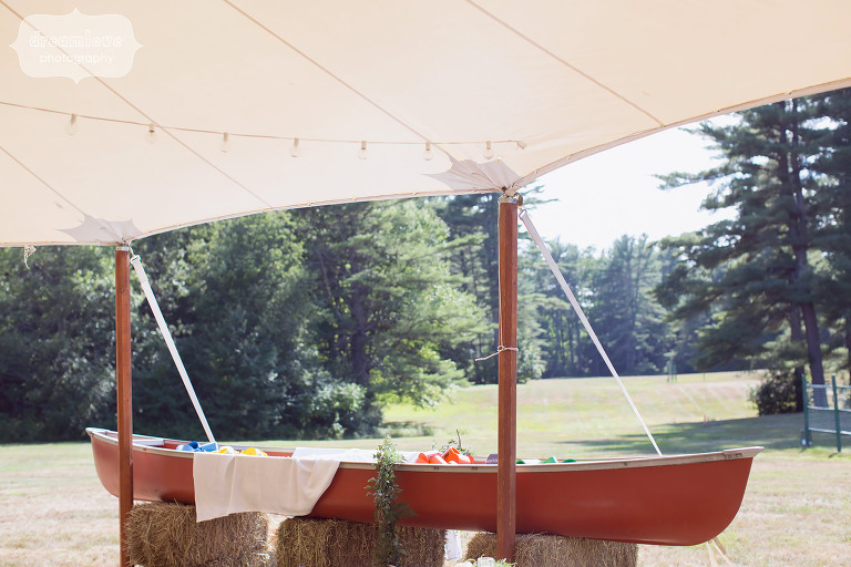 This red canoe was perfect rustic decor to hold beer and custom koozies at this camp wedding in NH.