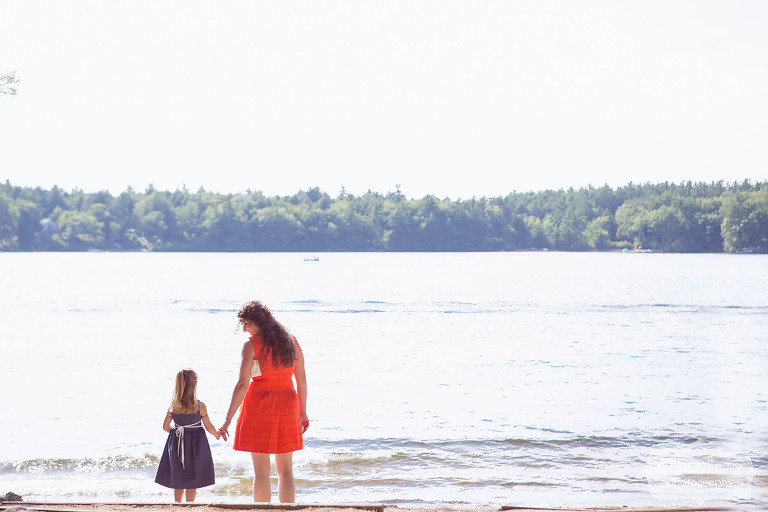 Love this candid moment we capture of a wedding guest holding a little girl's hand by the lake before the ceremony at the Woodbound Inn camp wedding in NH.