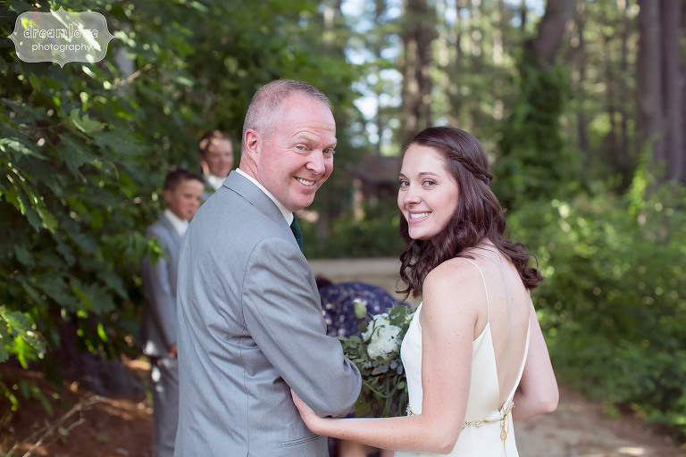 Great photo of the father of the bride and his daughter looking back before the wedding ceremony at this rustic camp wedding at the Woodbound Inn in NH.