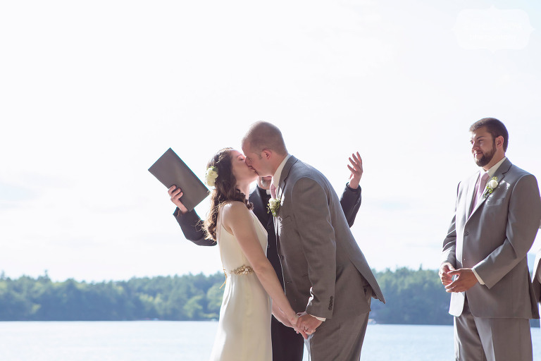This is a funny wedding kiss photo where the officiant put up both of his hands behind the couple just as they were kissing at the Woodbound Inn, NH.