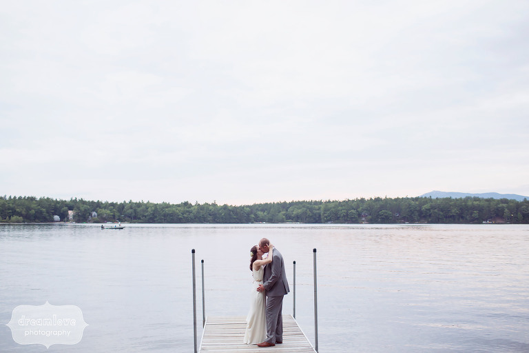 The bride and groom embracing on the dock at the Woodbound Inn in NH.