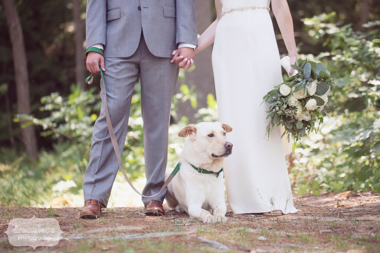 Great wedding photo of the bride and groom holding hands over their dog after the wedding ceremony at the Woodbound Inn in NH.