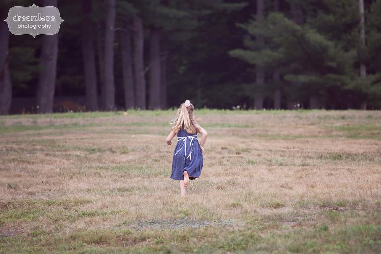 Fine art wedding photography girl running through field at the Woodbound Inn in NH.