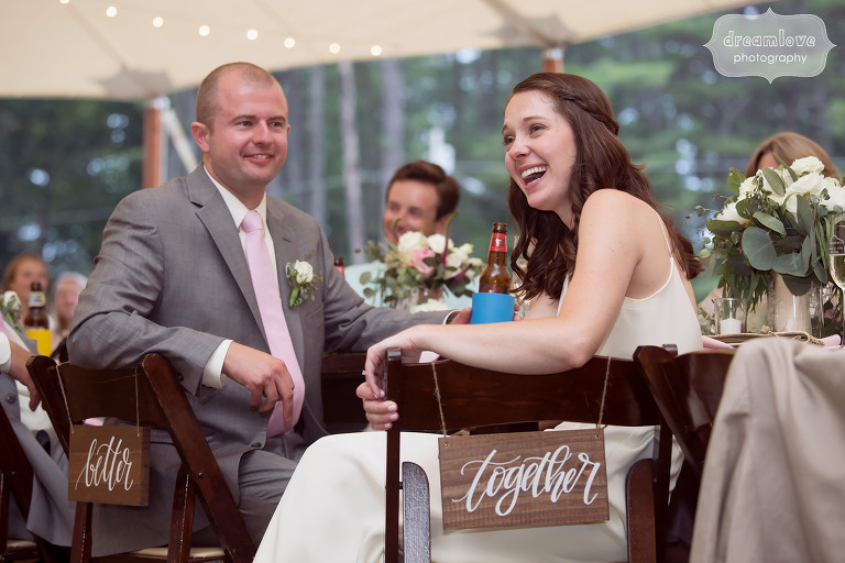 Journalistic wedding photography of the bride and groom listening and laughing during wedding speeches at the Woodbound Inn in NH.