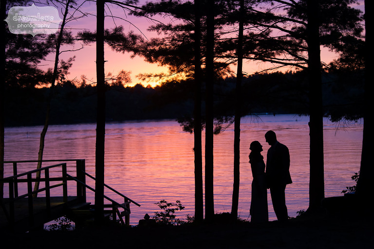 Sunset photo of the bride and groom with the lake behind them at the NH camp wedding venue the Woodbound Inn.