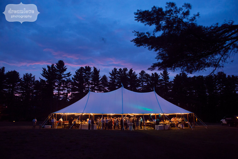 View of the sailcloth tent set up in the field at the Woodbound Inn in NH during sunset twilight.