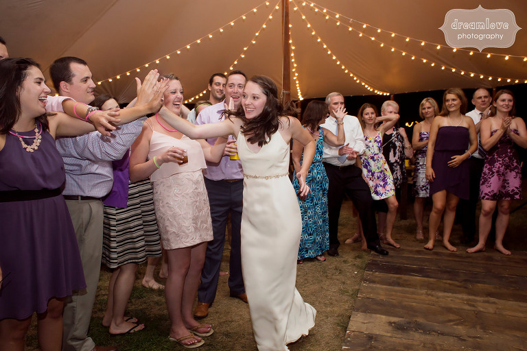 Great photo of the bride high fiving guests during this camp wedding at the Woodbound Inn in NH.