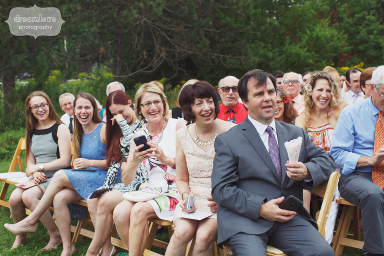 Wedding guests smiling during ceremony procession at Topnotch Resort in Stowe, VT.