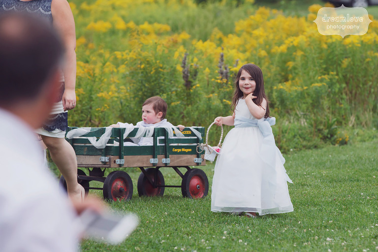 Adorable flower girl with ring bearer in wagon at Topnotch Resort in Stowe, VT.