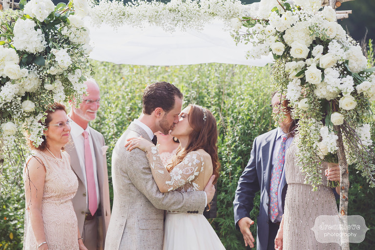 The bride and groom have their first kiss at the end of their ceremony in Stowe, VT.