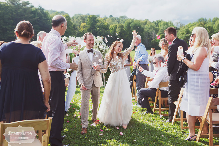 The bride and groom exit and wave while guests throw flower petals at Topnotch Resort in Stowe, VT.